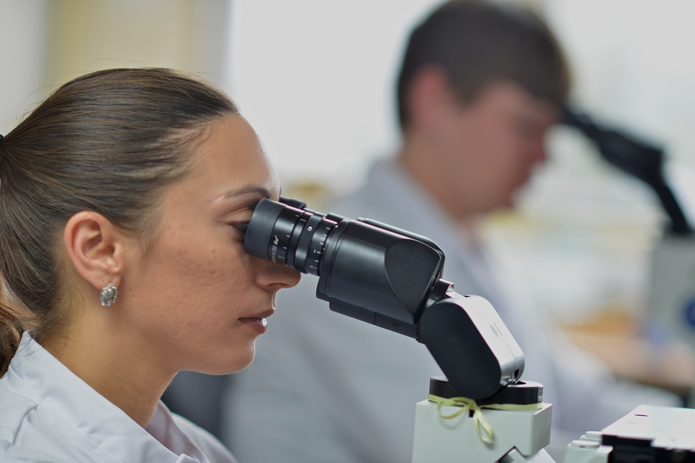 a group of people in lab coats looking at a scientific experiment in beakers