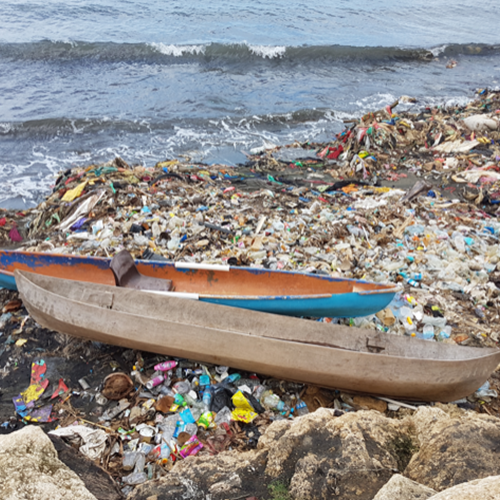 two boats on beach with lots of litter