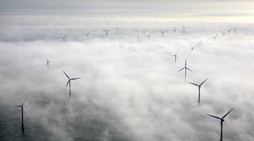 wind farm in sea in mist