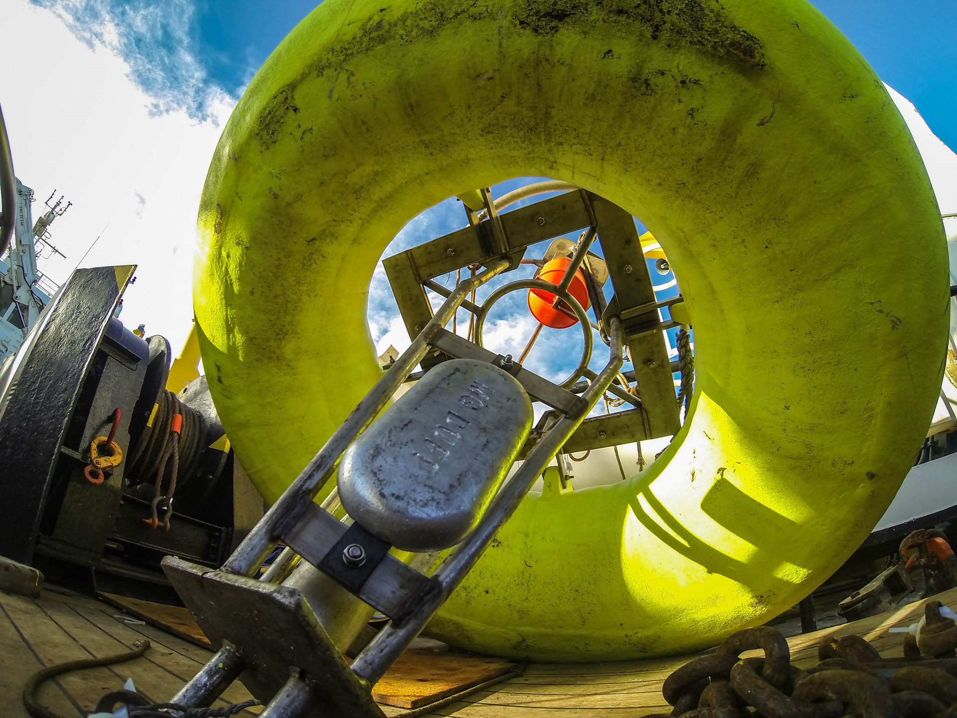 a yellow buoy containing scientific equipment on the deck of a boat